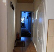 budynek wewnatrz, korytarz, z boku pokoje i naprzeciwko łazienki