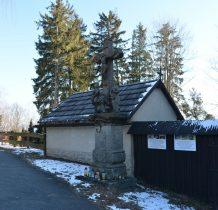 kamienna rzeźba Ukrzyżowanie i murowany budynek dawnej kostnicy